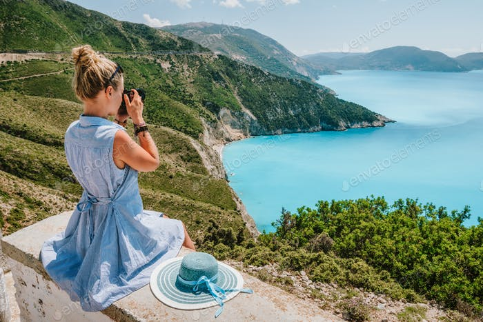 Attractive female tourist with camera enjoying seascape of Kefalonia, Greece