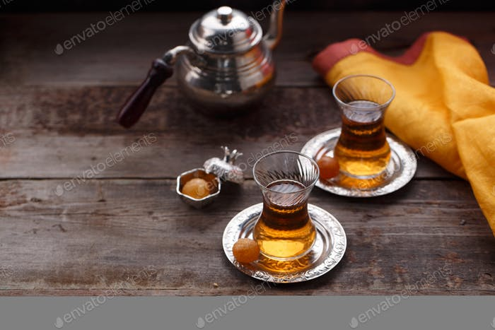 Traditional turkish teapot and cups of tea on woden background