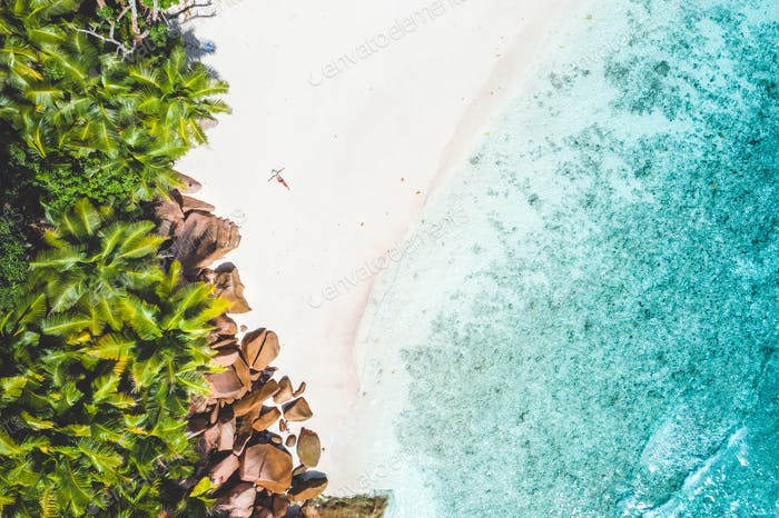 Aerial photo of exotic tropical white sand beach with young woman sunbathing relaxing. Concept of