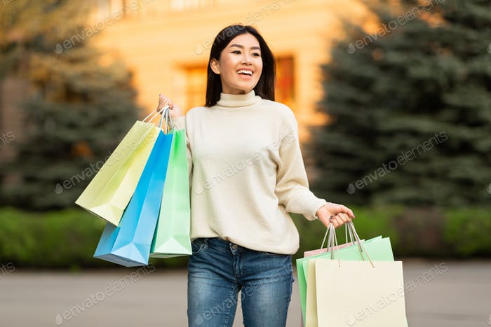 Asian girl with shopping bags near city center