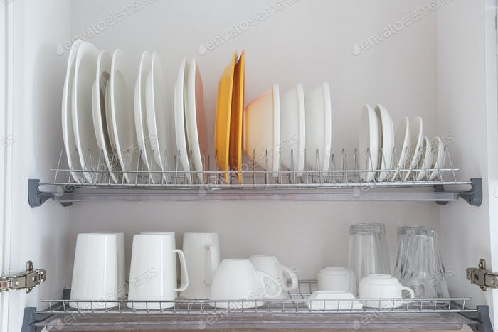 Dish drying metal rack with big nice white clean kitchenware. Traditional wall cabinet kitchen