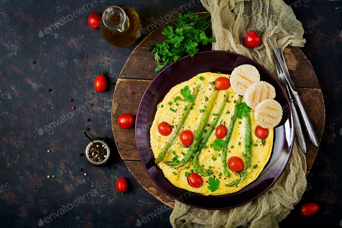 Omelette (omelet) with tomatoes, asparagus and green onions