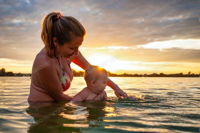 Woman teaching baby swimming in sea during sundown