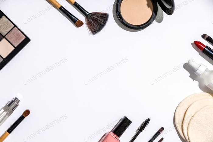 Makeup brushes and cosmetic products on a white background
