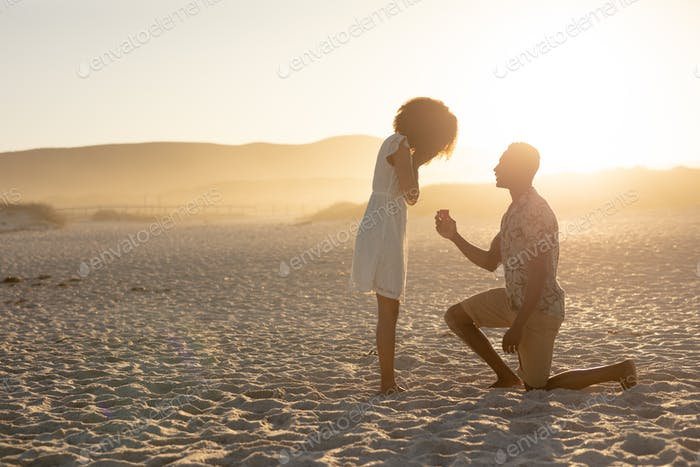 An African American man proposing to the woman on beach on a sunny day