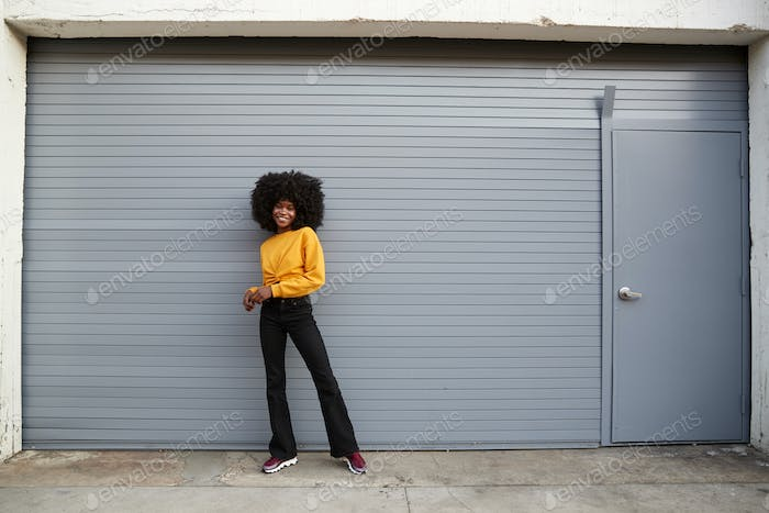 Hip young black woman standing against grey security shutters smiling to camera, full length
