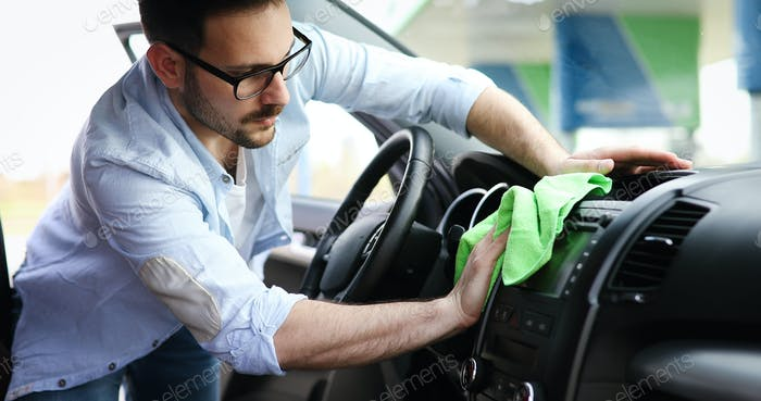 Person cleaning car with microfiber clot and maintaining shine