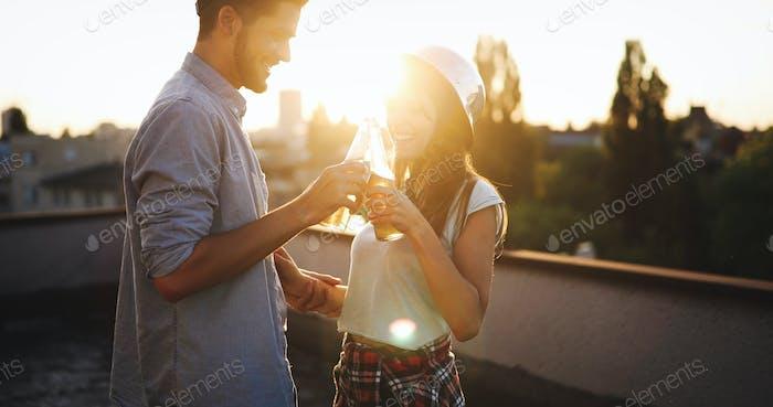 Happy young couple enjoying drinks and balcony