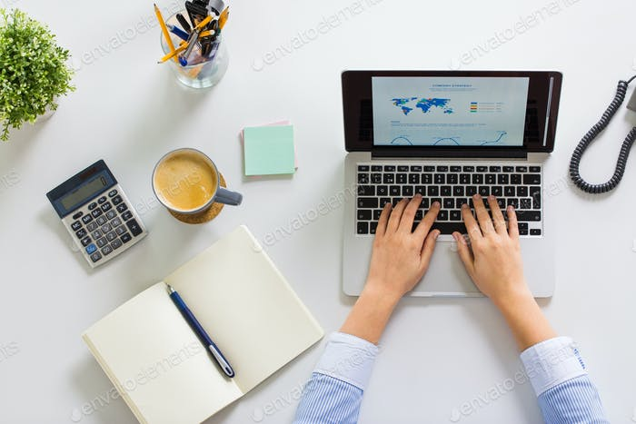 hands of businesswoman working on laptop at office