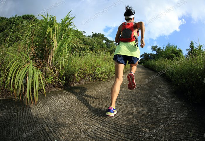 young fitness woman trail runner running on seaside mountain