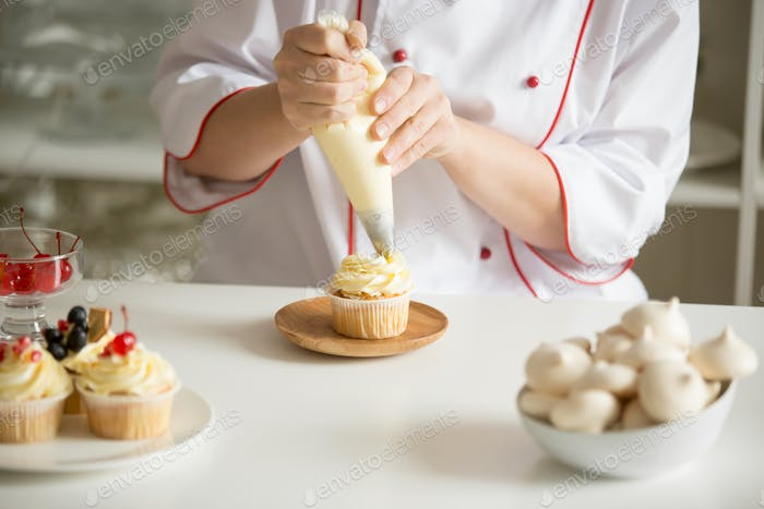 Close up of hands topping a cupcake with cream