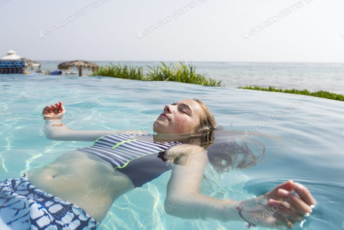 13 year old girl floating in infinity pool