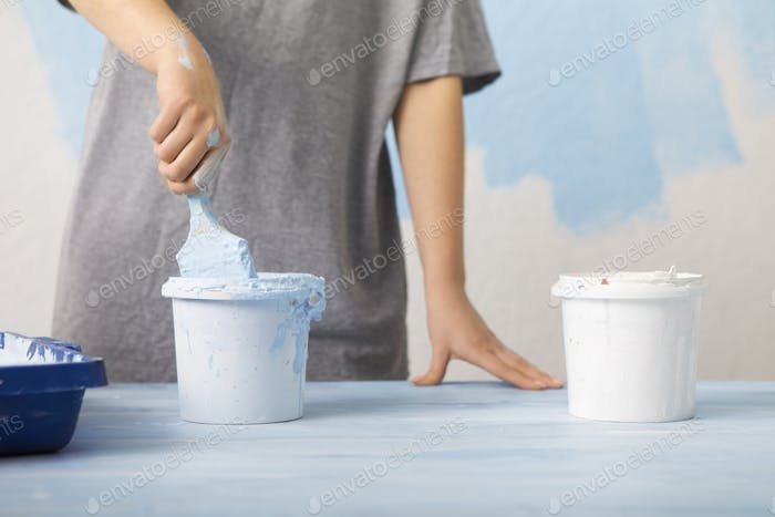 Woman mixing pigment and paint for wall painting