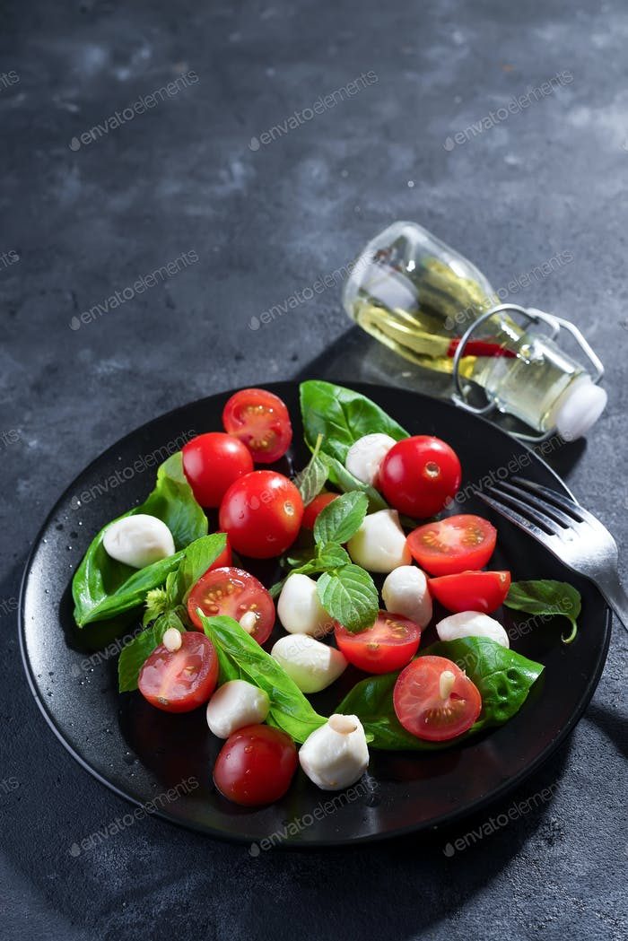 Italian caprese salad with sliced tomatoes, mozzarella cheese, basil, olive oil