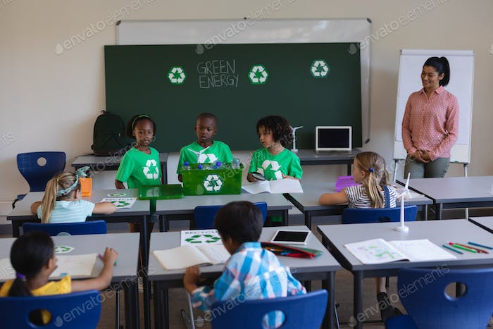 Schoolkids studying about green energy and recycle at desk in classroom of elementary school