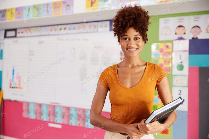 Portrait Of Female Elementary School Teacher Standing In Classroom