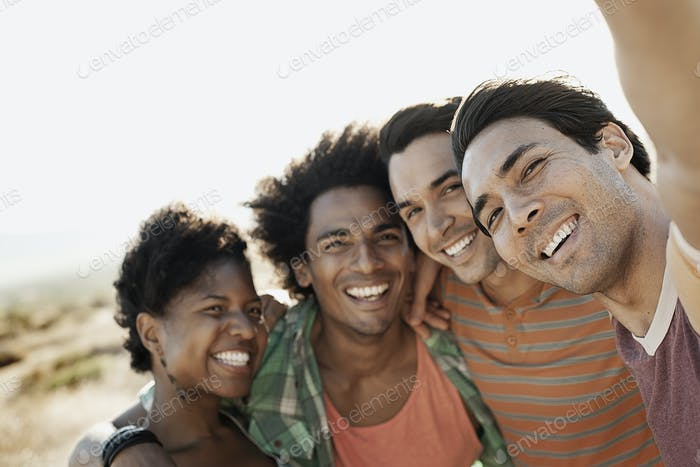 A group of friends, men and women, heads together posing for a selfy in the heat of the day.
