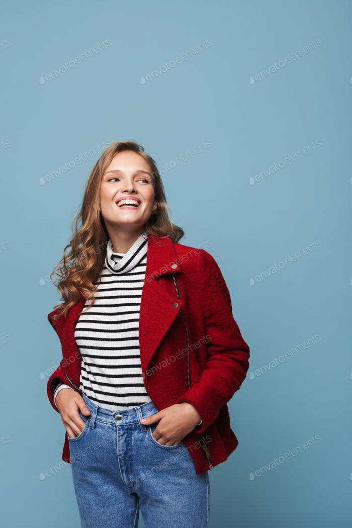 Joyful girl with wavy hair in red jacket and jeans happily looking aside holding hands in pockets