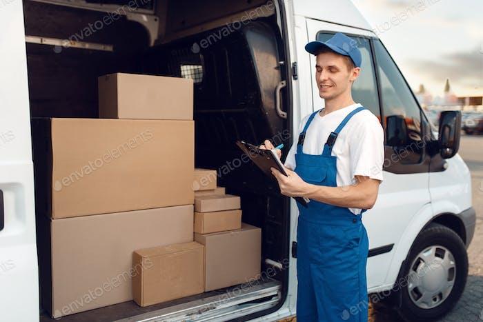 Deliveryman in uniform, carton boxes in the car