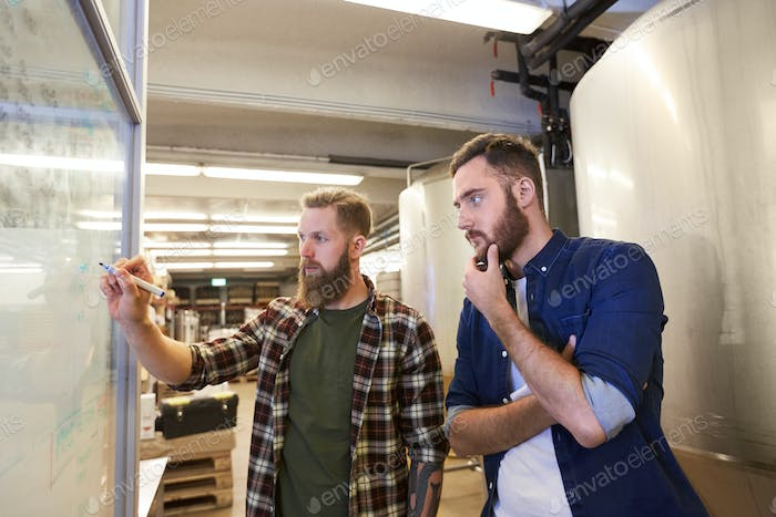 men writing on whiteboard at brewery or beer plant