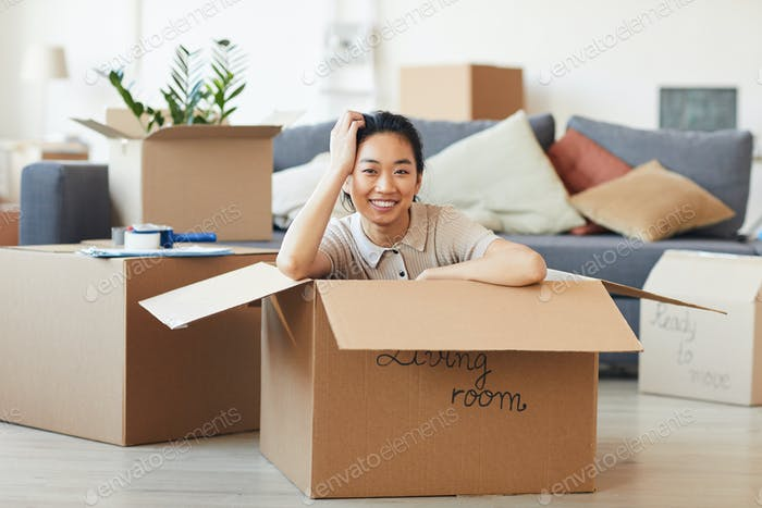 Smiling Asian Woman Sitting in Cardboard Box in New House