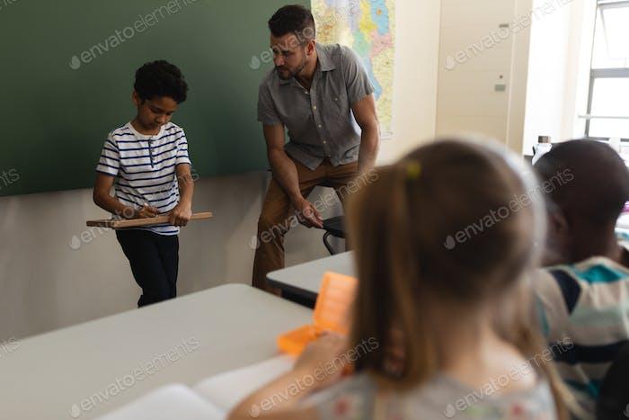 Schuljunge Schreiben auf Schieferbrett und Lehrer ihn im Klassenzimmer der Grundschule