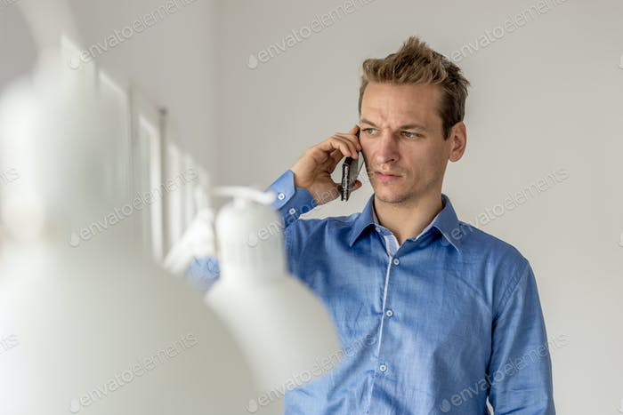 Businessman frowning as he speaks on mobile phone