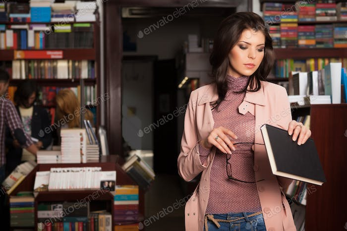 young caucasian brunette girl in a bookstore
