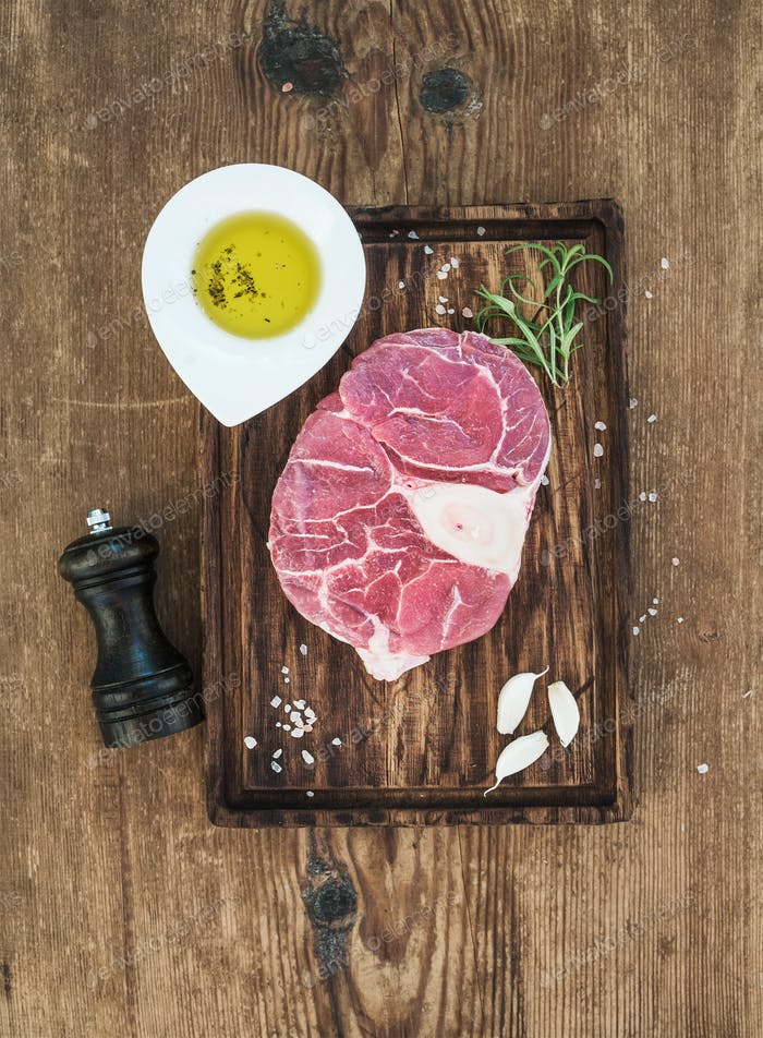 Raw fresh beef meat cross cut for ossobuco with garlic cloves, rosemary, pepper, oil and salt