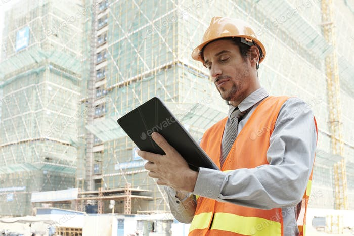 Architect using tablet pc outdoors