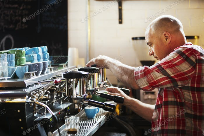 Specialist coffee shop. A man working a coffee machine making coffee.