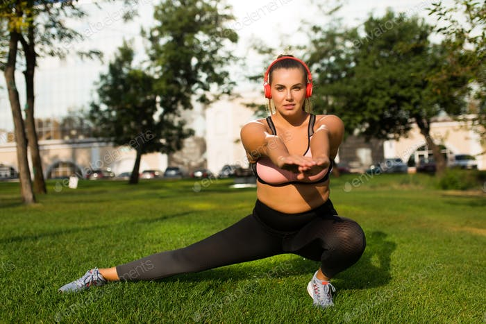 Young attractive plus size woman in sporty top and leggings with