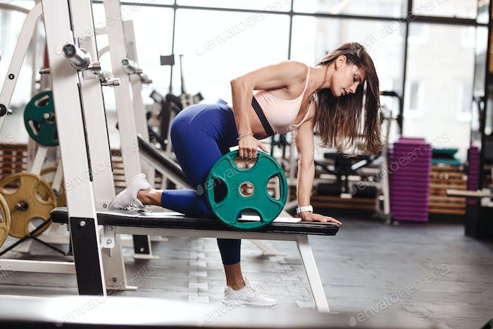 Young ahletic brunette girl dressed in a sportswear is doing exercises for back with plate on the