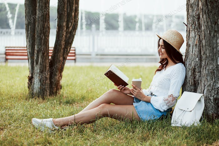 Smart brunette. Young woman have weekend and sits in the park at daytime