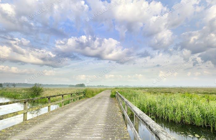 schöne Wolken über Brücke und Fluss
