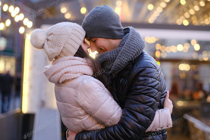 Romantic couple together in evening street near a cafe outside at Christmas time
