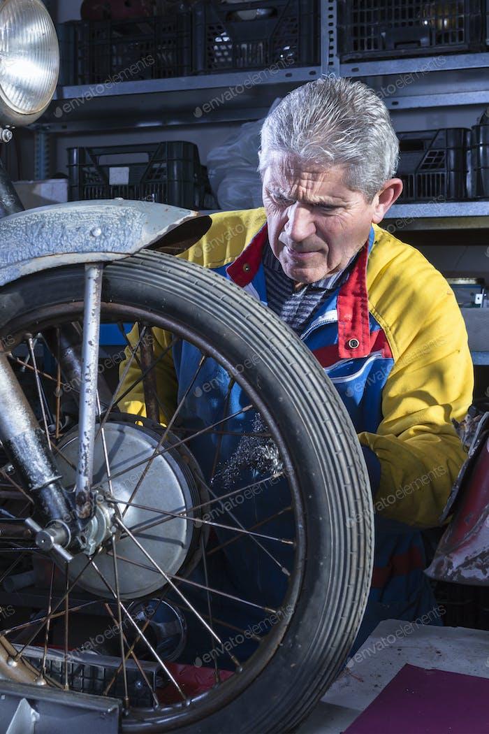 Mechaniker Schleifen der Motorradspeichen