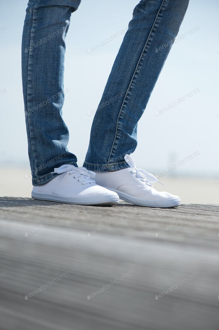 Female legs standing outdoors in comfortable white shoes
