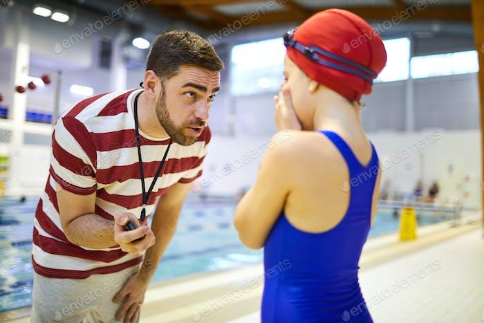 Swim instructor talking to athlete
