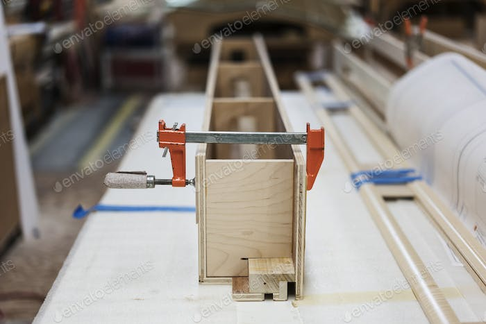 Close up of small bar clamps being used in a woodworking factory.