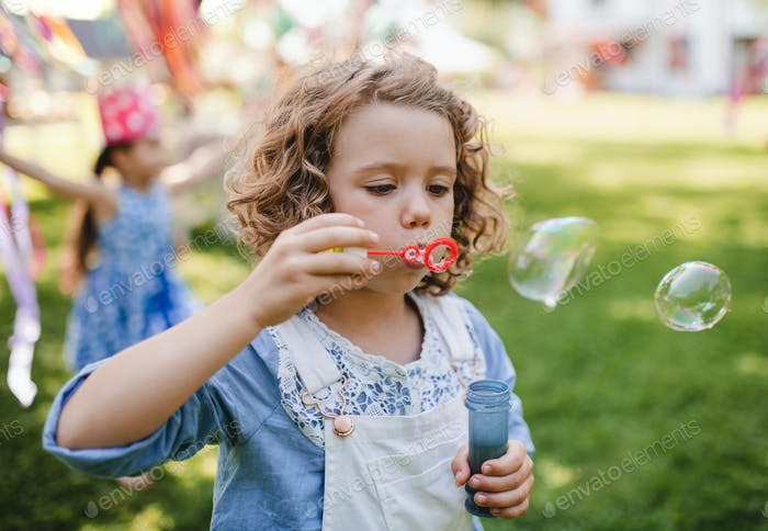 Small girl blowing bubbles outdoors in garden in summer.