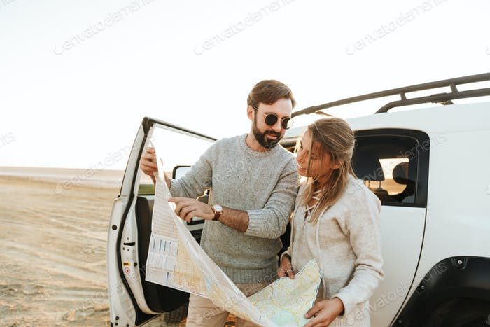 Atractiva pareja joven mirando el mapa del viaje