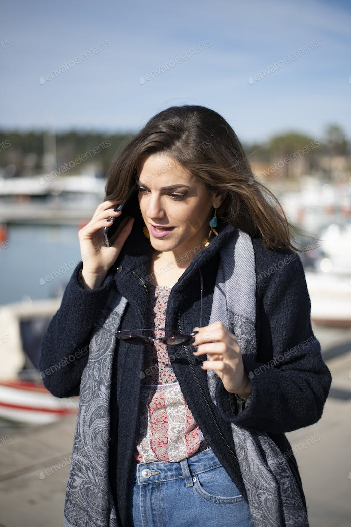 Business woman talking to the phone with her glasses on hand