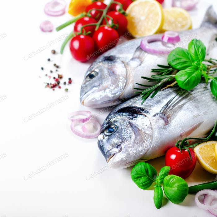 Fresh uncooked fish, dorado, sea bream with lemon, herbs, vegetables and spices on white background