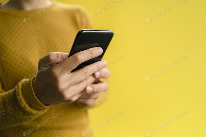 Woman in yellow sweater using smartphone