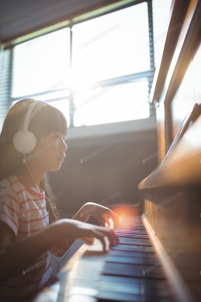 Concentrated girl looking at digital tablet while practicing piano