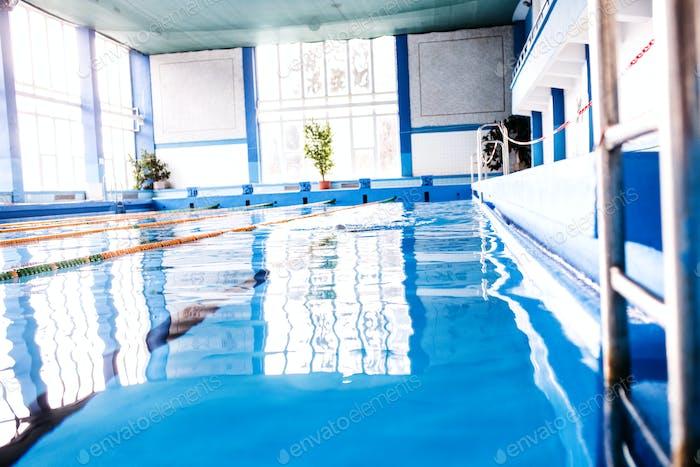 Senior man swimming in an indoor swimming pool.
