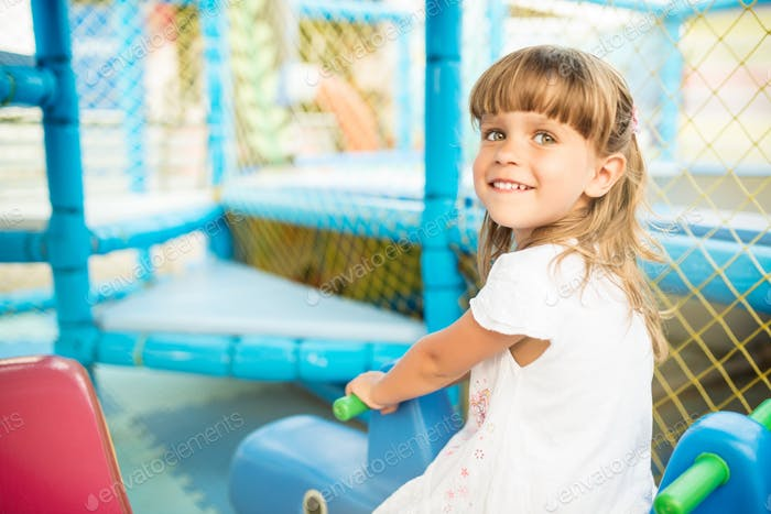 Funny girl in childrens entertainment center with toy