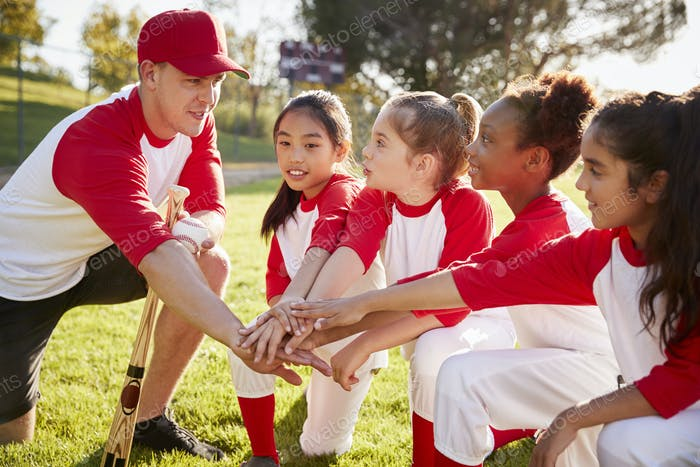 Girl baseball team kneeling with their coach, touching hands