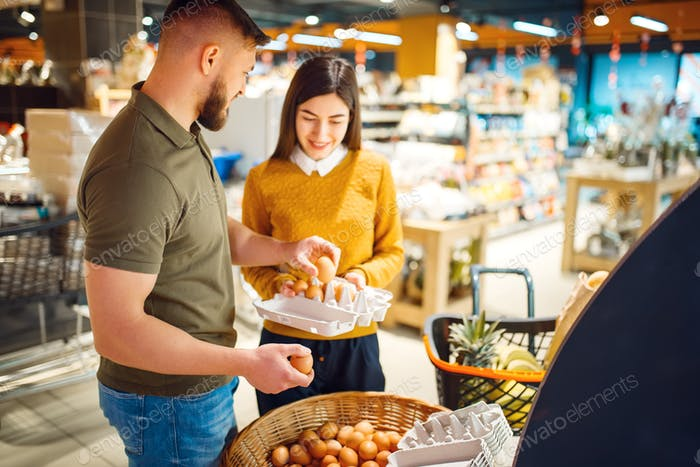 Family couple choosing eggs in grocery store